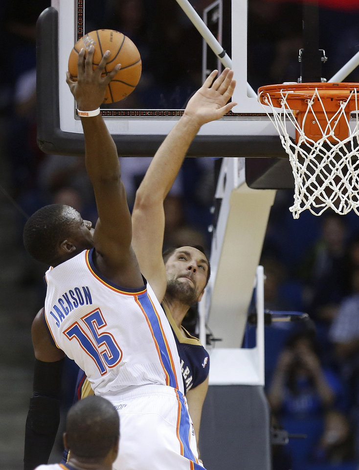 Oklahoma City Thunder guard Reggie Jackson (15) goes up for a dunk in front of New Orleans Pelicans forward Ryan Anderson during the first quarter of an NBA basketball preseason game in Tulsa, Okla., Thursday, Oct. 17, 2013. (AP Photo/Sue Ogrocki) ORG XMIT: OKSO112