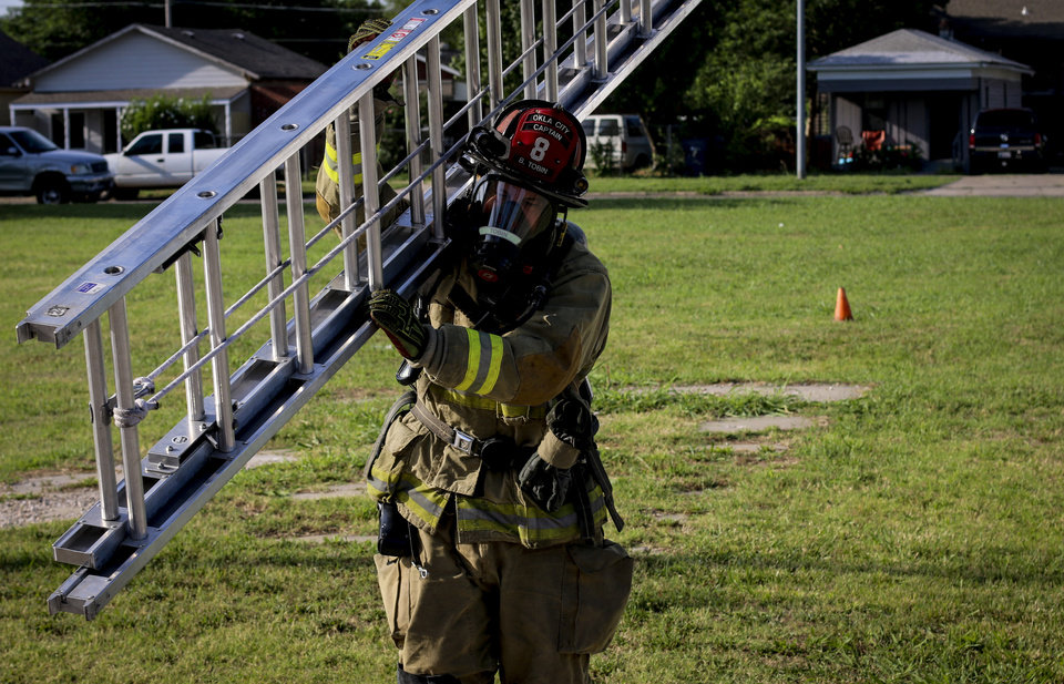 Photo -  Oklahoma City fire Capt. Brad Tobin carries a ladder during a morning workout and firefighter skills practice routine July 4 at Fire Station 8. [Photo by Cort Smith, for The Oklahoman]