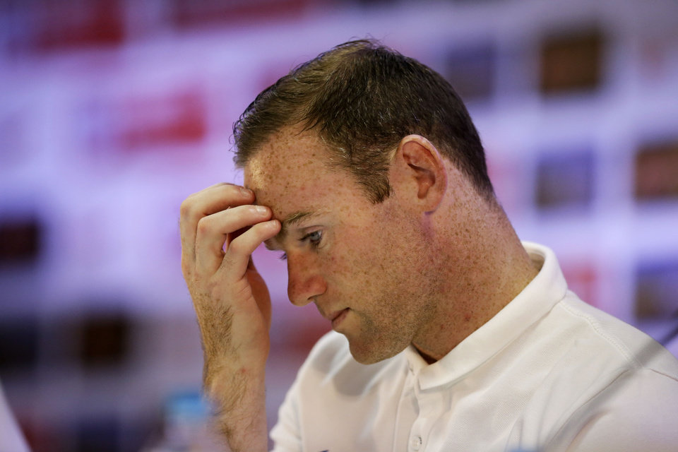 Photo - England national soccer team player Wayne Rooney holds his hand to his face during a press conference after a squad training session for the 2014 soccer World Cup at the Urca military base in Rio de Janeiro, Brazil, Saturday, June 21, 2014.  Costa Rica's surprise 1-0 win over Italy on Friday meant that England made its most humiliating exit from a World Cup since 1958, following consecutive defeats by the Italians and then Uruguay in Group D.  England play Costa Rica in their final Group D match on Tuesday.  (AP Photo/Matt Dunham)