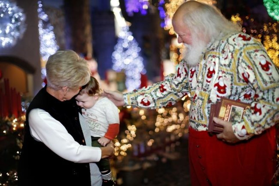 Photo -  Milo Proctor and his grandmother, Cynthia Fariss, are greeted by Dan Short, who portrays Santa Claus, as he walks through North Pole City, 4201 S Interstate 44 Service Road. [Sarah Phipps/The Oklahoman]
