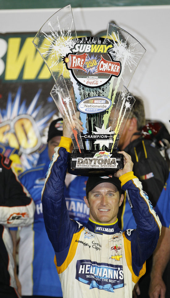 Photo - Kasey Kahne celebrates with his trophy in Victory Lane after winning the NASCAR Nationwide series auto race at Daytona International Speedway in Daytona Beach, Fla., Friday, July 4, 2014. (AP Photo/Terry Renna)