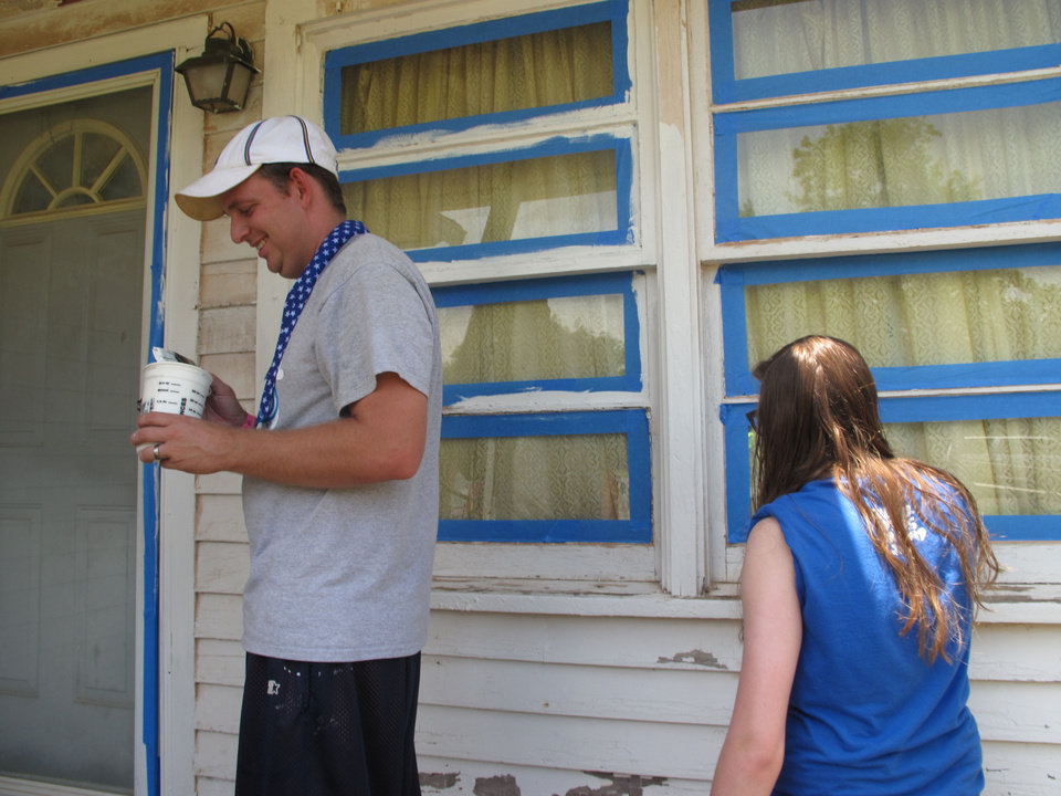 Photo - Chris Rathbone, a youth pastor from Eastland Assembly of God in Tulsa, paints trim on an Edmond home on Monday with the help of Halie (CQ) Pultz, 16, from Gateway Church in Southlake, Texas.  The Oklahoman - CARLA HINTON