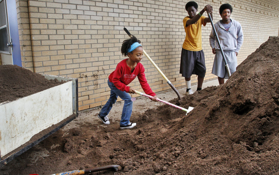 Photo - Amira Cooper, 7, a second-grader, uses a very small shovel to transfer soil into a trailer, to the amusement of two teens who take a break from loading the dirt. Volunteers were planting a garden at Stanley Hupfeld Academy. Photos by Jim Beckel, The Oklahoman