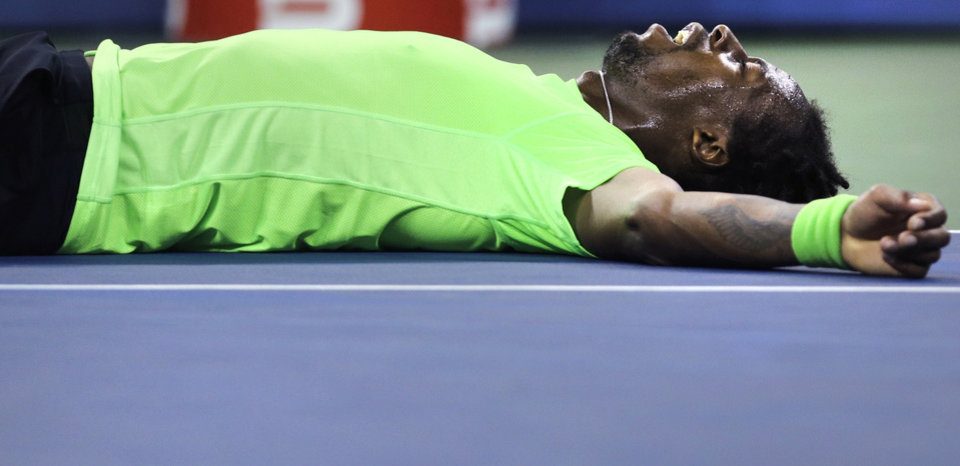 Photo - Gael Monfils, of France, lies on the court after taking a tumble on a return against Roger Federer, of Switzerland, during the quarterfinals of the U.S. Open tennis tournament, Thursday, Sept. 4, 2014, in New York. (AP Photo/Charles Krupa)