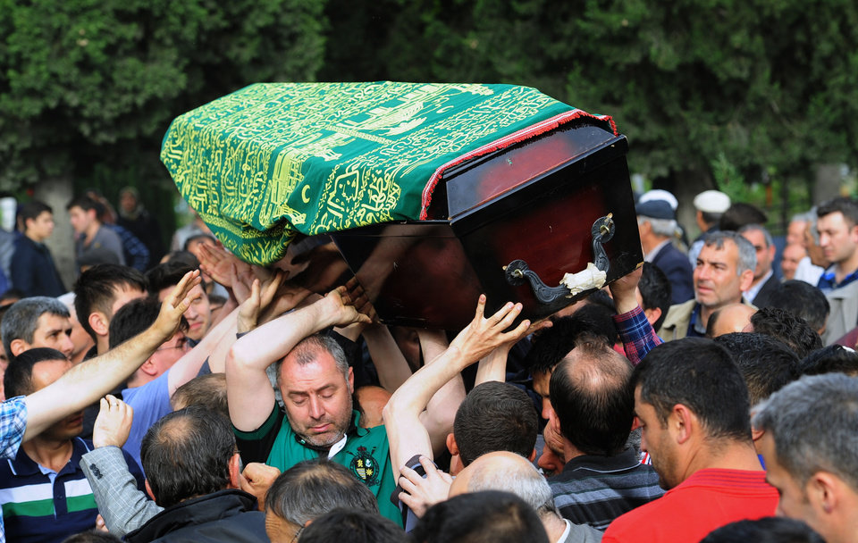 Photo - People bear a coffin aloft, of one mine accident victim for burial in Soma, Turkey, Wednesday, May 14, 2014.   Nearly 450 miners were rescued, the mining company said, but the fate of an unknown number of others remained unclear as bodies are still being brought to the surface and burials are underway after one of the world's deadliest mining disasters.(AP Photo/Emre Tazegul)