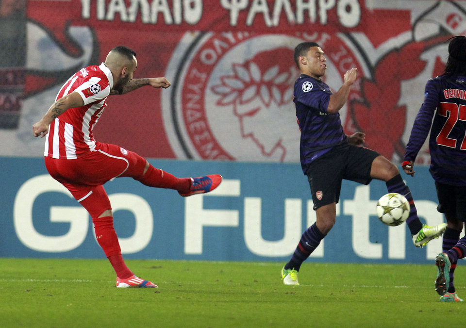 Olympiakos' Kostas Mitroglou, left, scores against Arsenal during a group B Champions League soccer match in the port of Piraeus, near Athens, Tuesday, Dec. 4, 2012. (AP Photo/Thanassis Stavrakis)