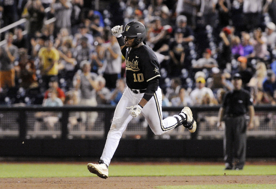 Photo - Vanderbilt's John Norwood celebrates as he runs the bases after hitting a home run against Virginia in the eighth inning of Game 3 of the best-of-three NCAA baseball College World Series finals in Omaha, Neb., Wednesday, June 25, 2014. (AP Photo/Eric Francis)