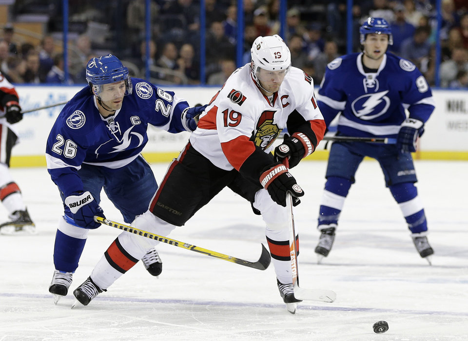 Photo - Ottawa Senators center Jason Spezza (19) cuts between Tampa Bay Lightning right wing Martin St. Louis (26) and center Tyler Johnson (9) during the first period of an NHL hockey game Thursday, Jan. 23, 2014, in Tampa, Fla. (AP Photo/Chris O'Meara)