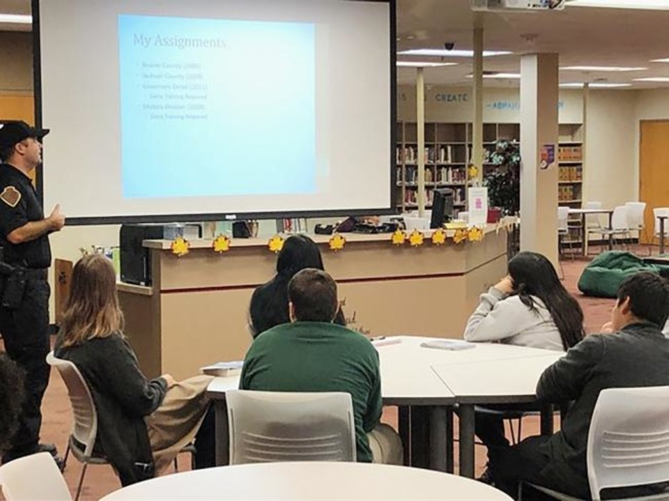 Photo -  Oklahoma Highway Patrol trooper Scott Beaman, representing the law enforcement profession, makes a presentation to students at Harding Charter Preparatory High School. [PROVIDED]