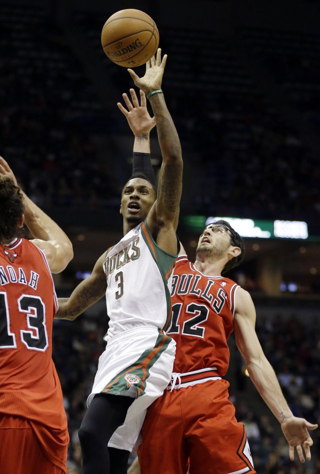 Milwaukee Bucks' Brandon Jennings (3) puts up a shot against Chicago Bulls' Kirk Hinrich (12) and Joakim Noah (13) during the second half of an NBA basketball game Wednesday, Jan. 30, 2013, in Milwaukee. (AP Photo/Jeffrey Phelps)