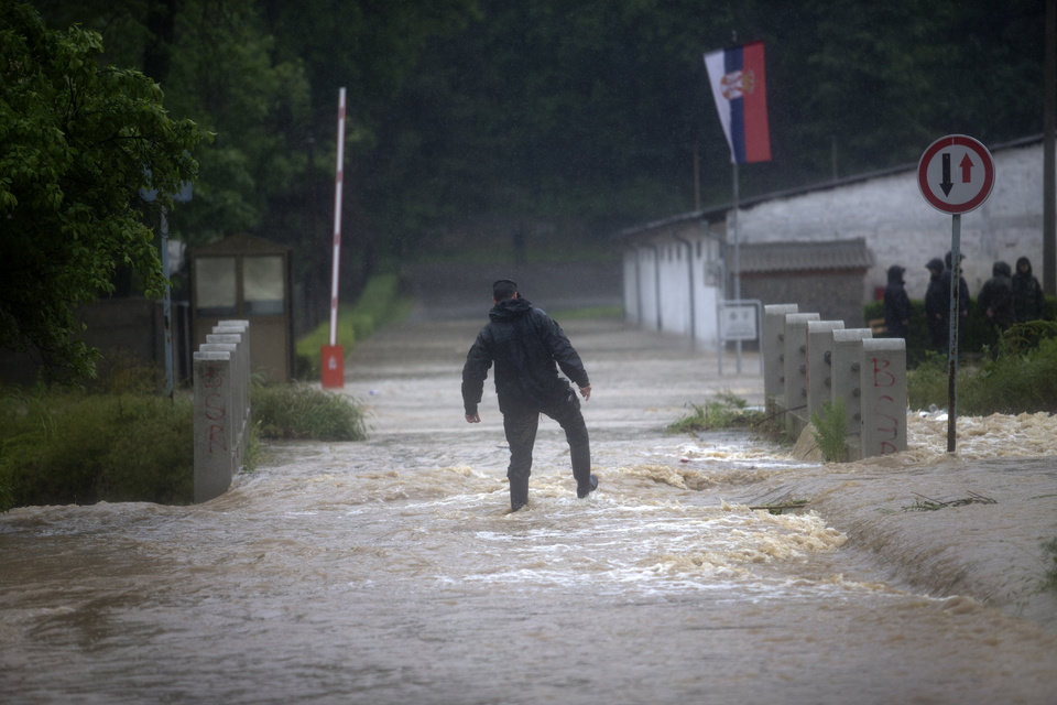 Photo - A police officer struggles as he walks along a flooded street in a suburb of Belgrade, Serbia, Thursday, May 15, 2014.  Some hundreds of people have been evacuated from their homes as floods caused by heavy rains gripped the Balkans Thursday, overflowing roads, bridges and railways, closing down schools, and cutting off power supplies and phone lines. (AP Photo/Marko Drobnjakovic)