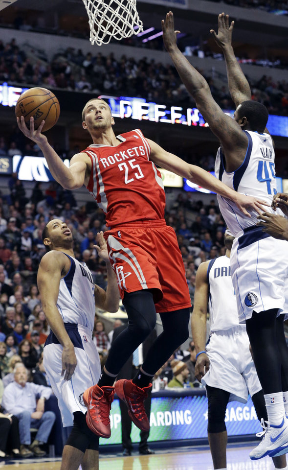 Photo - Houston Rockets forward Chandler Parsons (25) drives to the basket between Dallas Mavericks center DeJuan Blair (45) and Devin Harris during the second half of an NBA basketball game Wednesday, Jan. 29, 2014, in Dallas. Parsons scored a team high 26 points in the Rockets 117-115 win. (AP Photo/LM Otero)