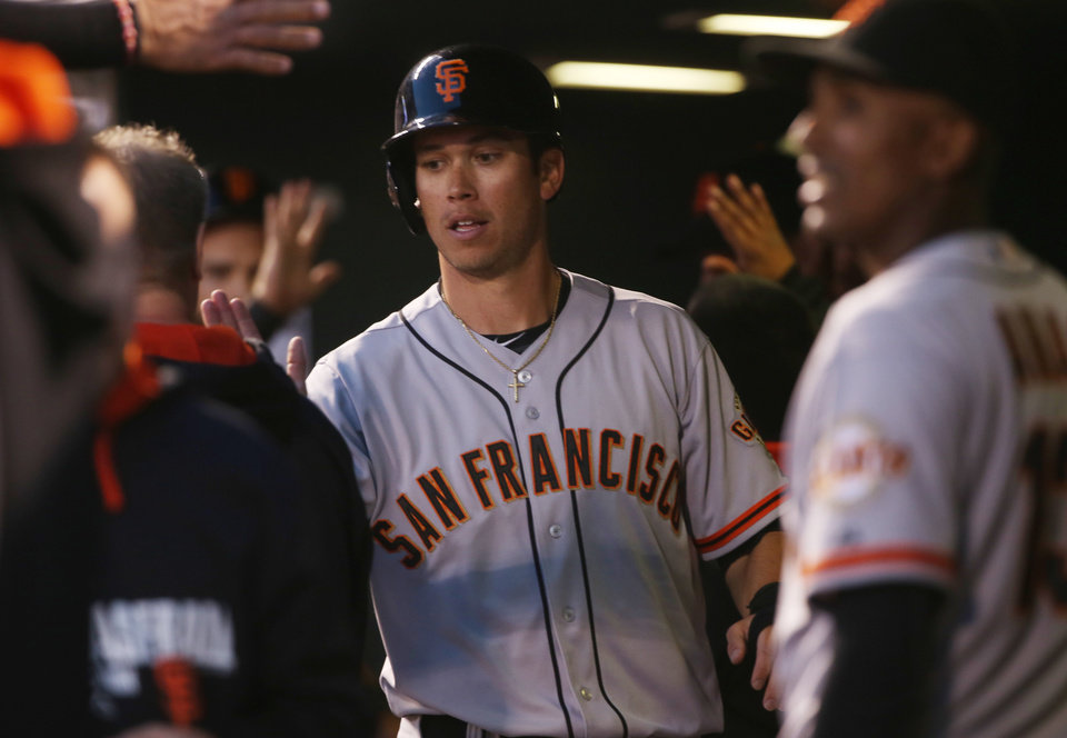 Photo - San Francisco Giants' Tyler Colvin is congratulated by teammates after scoring on a triple by Gregor Blanco against the Colorado Rockies in the fifth inning of a baseball game in Denver on Tuesday, May 20, 2014. (AP Photo/David Zalubowski)