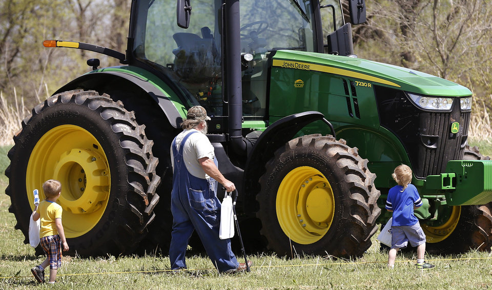 Photo -  A man and two boys approach a farm tractor to get a closer look during the Oklahoma Cooperative Extension Service Whistle-Stop and Festival on Saturday in Wellston. Photo by Jim Beckel, The Oklahoman   Jim Beckel -