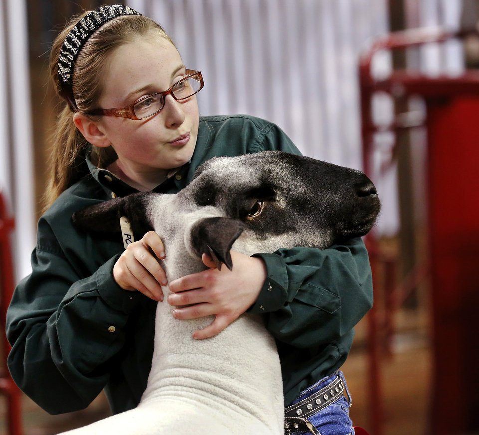 Photo -  Abby Cardwell, 11, with Deer Creek-Lamont 4-H Club, shows her sheep.   Jim Beckel -