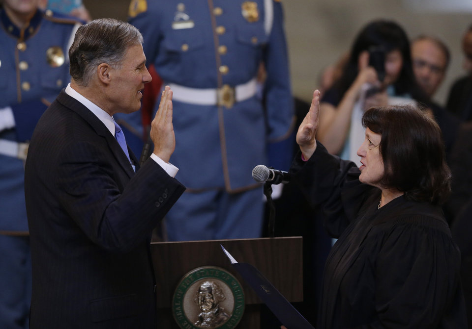 Jay Inslee, left, is sworn in as Washington state Governor, Wednesday, Jan. 16, 2013, by Washington Supreme Court Chief Justice Barbara Madsen, right, in the rotunda of the Legislative Building at the Capitol in Olympia, Wash. (AP Photo/Ted S. Warren)