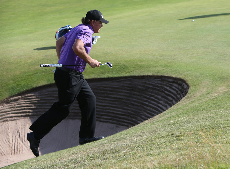 Photo - Phil Mickelson of the US runs past a bunker to play a putt on the 13th green during the first day of the British Open Golf championship at the Royal Liverpool golf club, Hoylake, England, Thursday July 17, 2014. (AP Photo/Scott Heppell)