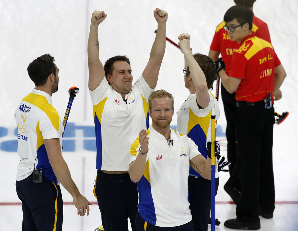 Photo - Sweden's player from left, Sebastian Kraup, Fredrik Lindberg, Niklas Edin, and Viktor Kjaell celebrate their victory over China in the men's curling bronze medal game at the 2014 Winter Olympics, Friday, Feb. 21, 2014, in Sochi, Russia. (AP Photo/Robert F. Bukaty)