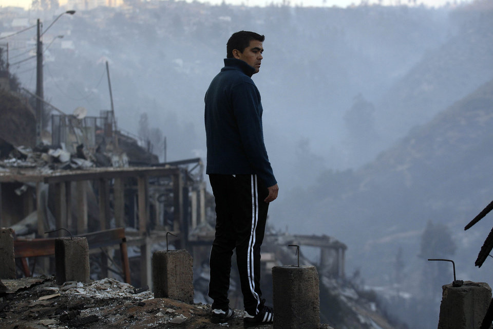 Photo - A man looks at the charred remains of homes after a large forest fire reached urban areas in Valparaiso, Chile, Sunday April 13, 2014. Authorities say the fires have destroyed hundreds of homes, forced the evacuation of thousands and claimed the lives of at least seven people.  ( AP Photo/ Luis Hidalgo)