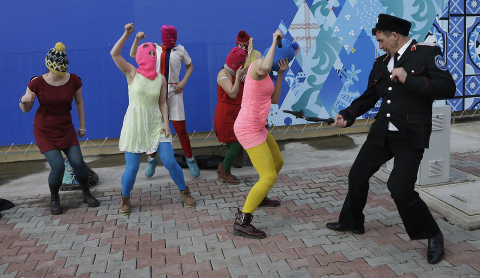 Photo - A Cossack militiaman attacks Nadezhda Tolokonnikova as she and fellow members of the punk group Pussy Riot, including Maria Alekhina, center, in the pink balaclava, stage a protest performance in Sochi, Russia, on Wednesday, Feb. 19, 2014. The group had gathered in a downtown Sochi restaurant, about 30km (21miles) from where the Winter Olympics are being held. They ran out of the restaurant wearing brightly colored clothes and ski masks and were set upon by about a dozen Cossacks, who are used by police authorities in Russia to patrol the streets. (AP Photo/Morry Gash)