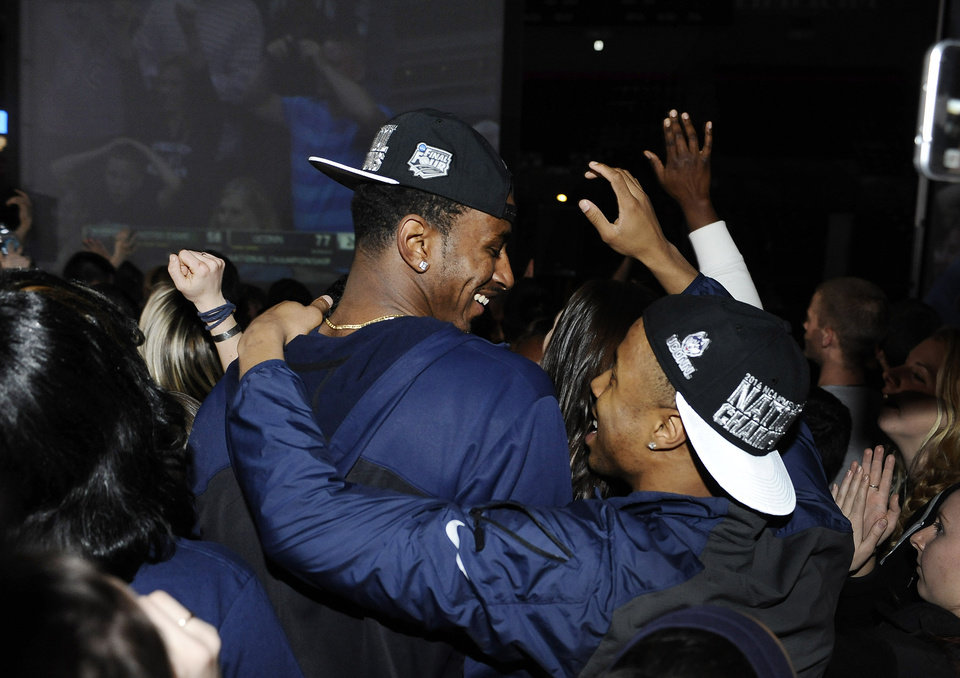 Photo - Connecticut men's basketball players DeAndre Daniels, left, and Tor Watts celebrate as they watch television coverage of the final seconds the UConn women's team's 79-58 win over Notre Dame in the NCAA women's college basketball tournament title game, Tuesday, April 8, 2014, in Storrs, Conn. (AP Photo/Jessica Hill)
