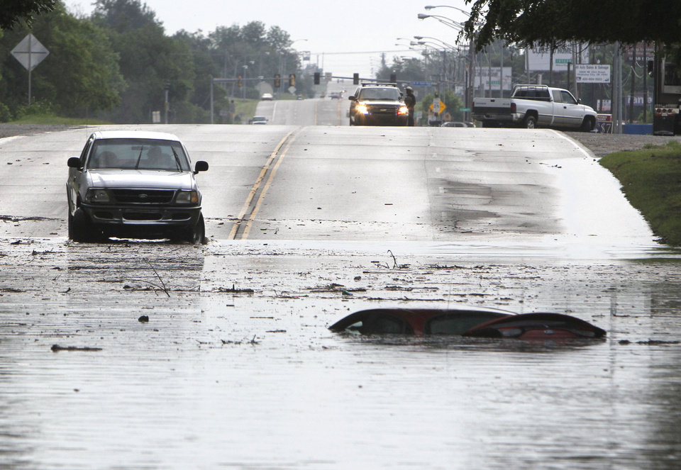 Photo - A car is submerged in floodwaters between Sooner Rd. and Air Depot Blvd. on NE 23rd St. in Midwest City, OK, Saturday, June 1, 2013, after up to eight inches of rain fell during the previous 24 hours. Photo by Paul Hellstern, The Oklahoman