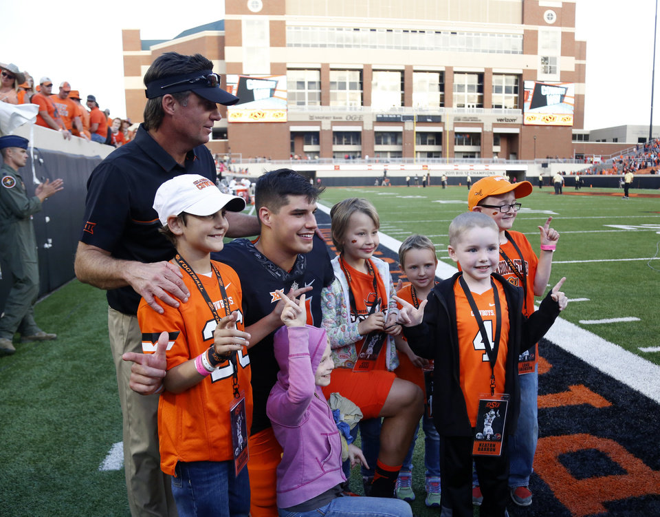 Photo - Oklahoma State head coach Mike Gundy and Mason Rudolph (2) take pictures with children from Coaches v Cancer following a college football game between the Oklahoma State University Cowboys (OSU) and the Iowa State University at Boone Pickens Stadium in Stillwater, Okla., Saturday, Oct. 8, 2016. Photo by Sarah Phipps, The Oklahoman