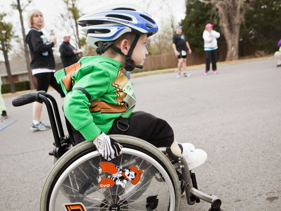Photo -  Four-year-old Ryder Gibson races from the starting line in his third wheelchair 5k of the Redbud Classic at Nichols Hills Plaza in Nichols Hills, OK, Sunday, April 6, 2014. Photo by KT King, The Oklahoman