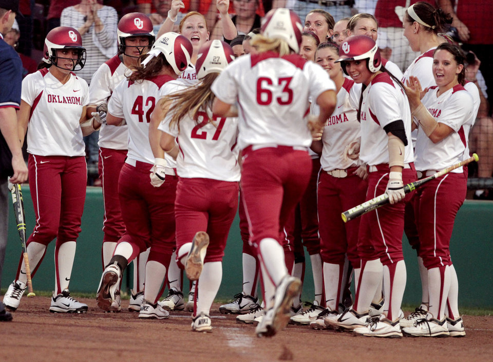 Sooner Erica Sampson (63) and the two runners she drove in are greeted at home plate after a home run with two base runners on as the University of Oklahoma (OU) Sooners play the Oklahoma State University Cowgirls in NCAA college softball at Marita Hines Field on Wednesday, April 25, 2012, in Norman, Okla. Photo by Steve Sisney, The Oklahoman