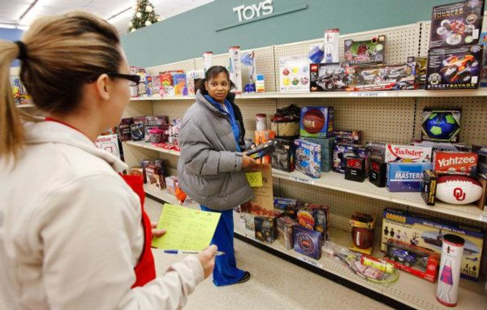 Photo - Kaye Wilson, right, asks a question to volunteer Rachel Madden while shopping for a gift for her 13-year-old son at the Christmas Connection in southwest Oklahoma City.  JIM BECKEL - THE OKLAHOMAN