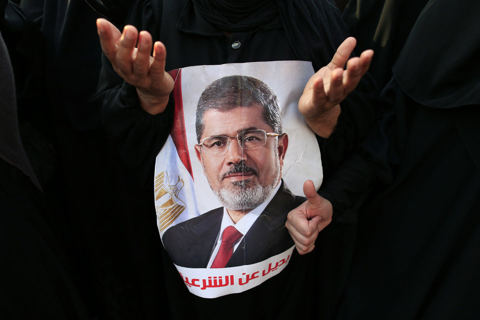Photo - Supporters of ousted President Mohammed Morsi pray in Nasr City, Cairo, Egypt, Tuesday, July 9, 2013. Arabic reads,