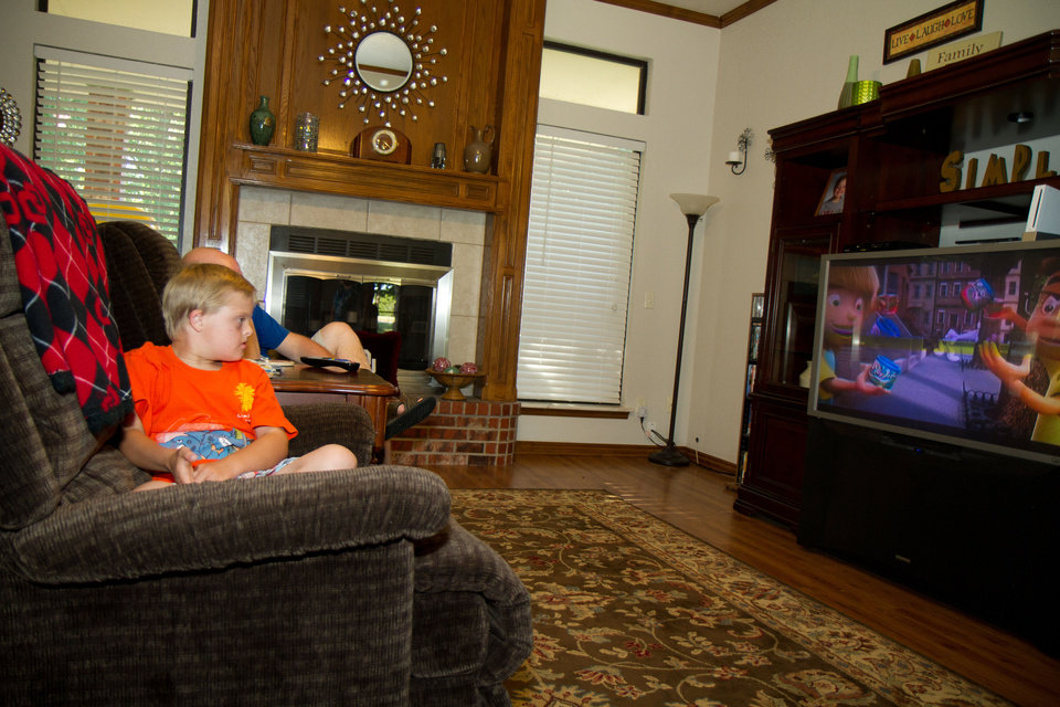 Photo - Lori Wathen and her 9-year-old son, Reis watch the start of the Thunder game at their home in Norman Thursday, May 31, 2012. Photo by Steven Maupin, for The Oklahoman