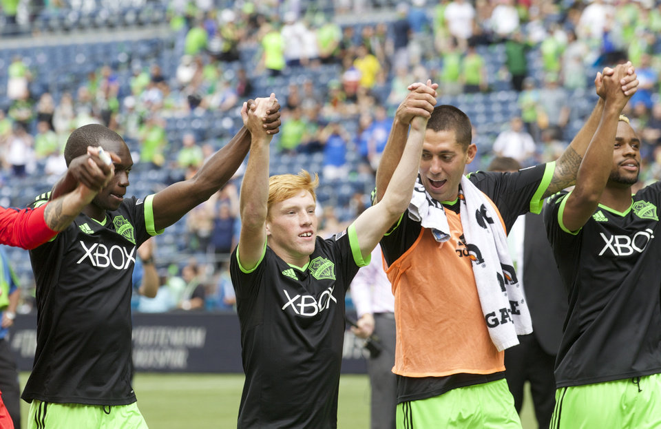 Photo - Along with Seattle Sounders teammates Jalil Anibaba, far left, Clint Dempsey, second from right, and Tristan Bowen far right, Xander Bailey acknowledges fans following a friendly soccer match against Tottenham Hotspur in Seattle, Saturday, July 19, 2014. The match ended in a 3-3 draw. (AP Photo/Stephen Brashear)
