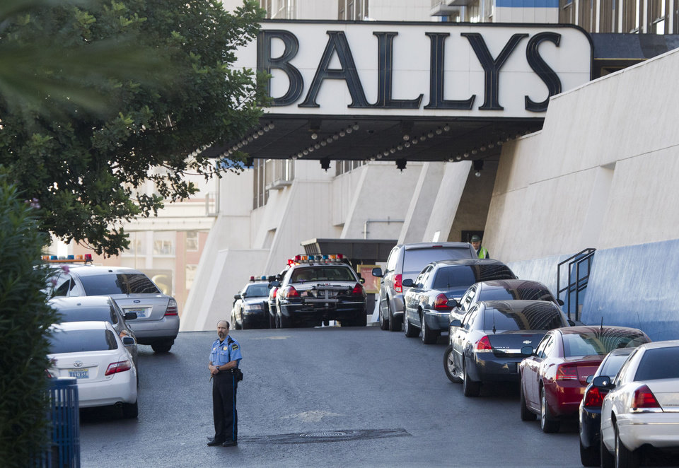 Photo - Las Vegas Metro Police cars and a hotel security officer are shown in front of Bally's hotel-casino after an early morning shooting left one person killed and two wounded in Drai's, a nightclub inside Bally's, in Las Vegas, Monday, Oct. 21, 2013. A suspect is in custody, police said. (AP Photo/Las Vegas Sun/Steve Marcus)