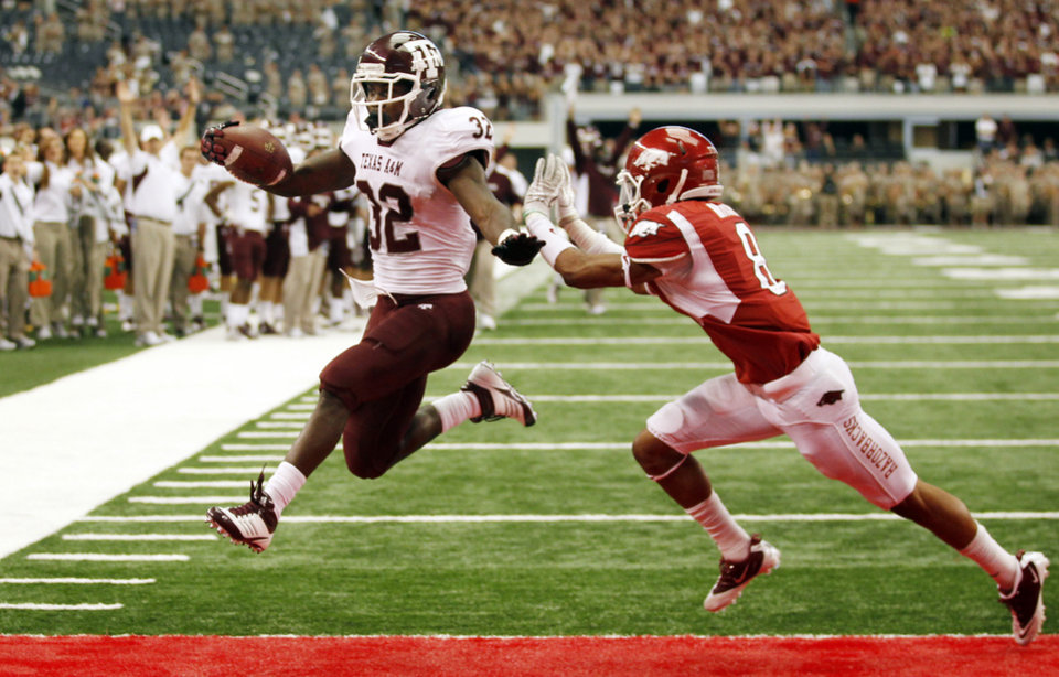 Texas A&M running back Cyrus Gray (32) leaps into the end zone for the team's fourth touchdown as Arkansas cornerback Tevin Mitchel (8) defends during an NCAA college football game on Friday, Sept. 30, 2011, at Cowboys Stadium in Arlington, Texas. (AP Photo/John F. Rhodes) ORG XMIT: CBS104