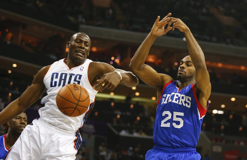 Photo - Philadelphia 76ers guard Elliot Williams (25) has a rebound knocked away by Charlotte Bobcats center Bismack Biyombo, left, during the first half of an NBA basketball game in Charlotte, N.C., Saturday, April 12, 2014. (AP Photo/Chris Keane)