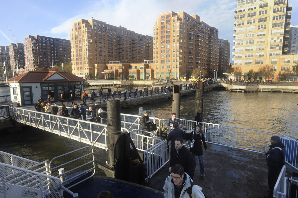 Commuters board a New York Waterway ferry bound for Midtown Manhattan at the 14th Street pier Thursday Nov. 1, 2012 in Hoboken, N.J. New York City moved closer to resuming its frenetic pace by getting back its vital subways Thursday, three days after a superstorm, but neighboring New Jersey was stunned by coastal devastation and the news of thousands of people in one city still stranded by increasingly fetid floodwaters. (AP Photo/Joe Epstein)