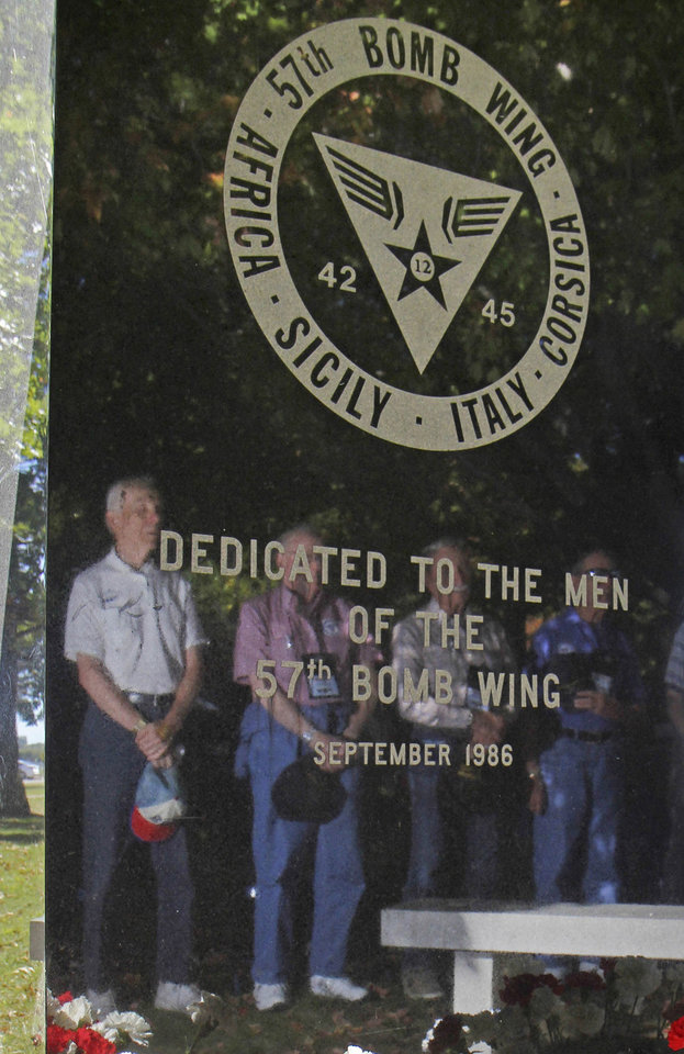 Photo - In this Sept. 27, 2013 photo, World War II veterans from the 57th Bomb Wing are reflected in the stone memorial to the wing during a reunion outside the U.S. Air Force Museum at Wright Patterson Air Force base in Dayton, Ohio. As many as 11,000 people served in the 57th that flew missions over German-held Europe from North Africa and the island of Corsica during most of the war. Hundreds survive, according to wing historians and reunion organizers. (AP Photo/Tom Uhlman)