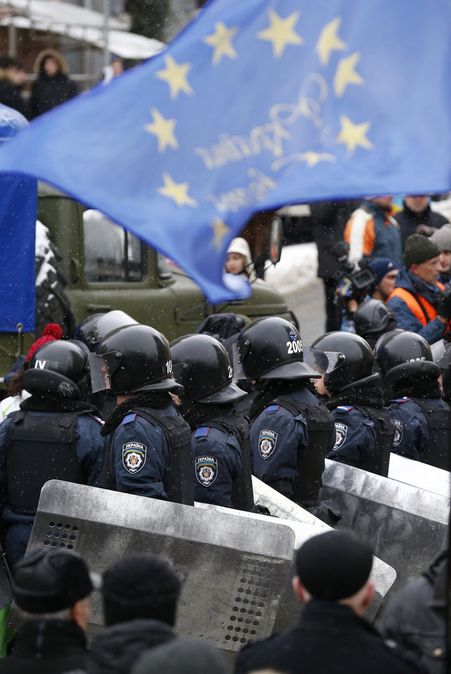 Photo - A EU flag waves over Ukrainian riot police officers as they prepare to block Pro-European Union activists gathered at the Independence Square in Kiev, Ukraine, Monday, Dec. 9, 2013. The policemen, wearing helmets and holding shields, formed a chain across Kiev's main street outside the city building. Organizers called on protesters to vacate the city hall and the other building which the opposition had used as its headquarters. (AP Photo/Alexander Zemlianichenko)