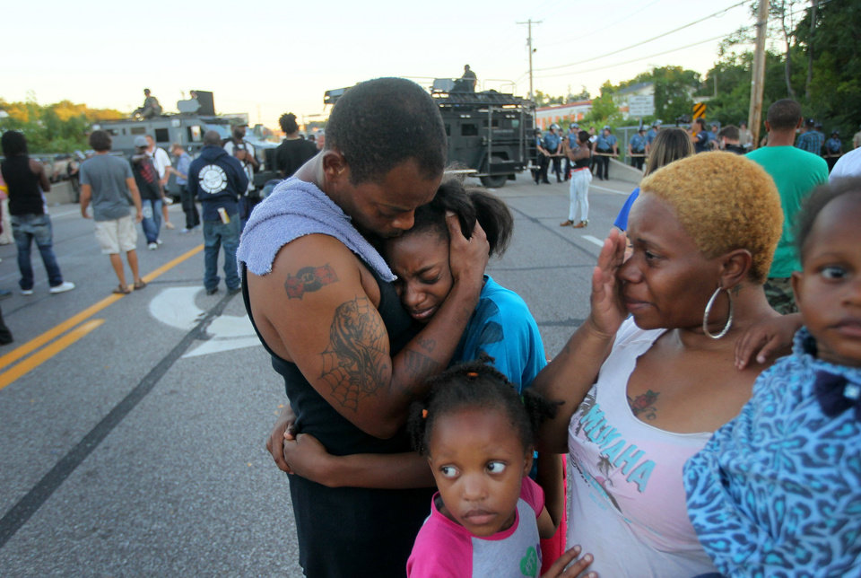 """Photo - Terrell Williams E hugs his daughter Sharell, 9, while standing with his wife, Shamika Williams, and daughters Tamika, 6, and Sharell, 2, on Wednesday, Aug. 13, 2014, in Ferguson, Mo. They were overcome with emotion after Williams El confronted police. """"I'm out here to stand for my children and their future,"""" said Williams El. (AP Photo/St. Louis Post-Dispatch, David Carson)"""