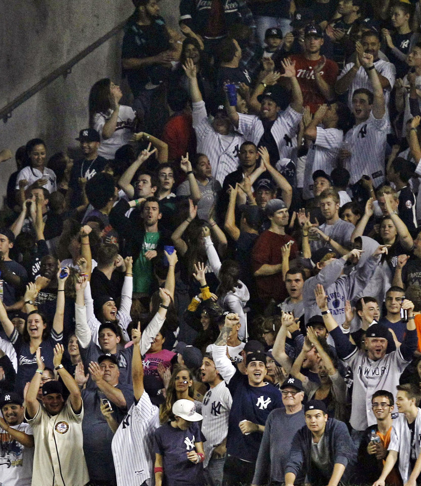Photo -   New York Yankees fans react in the seventh inning as the Yankees clinched the American League East title thanks to the Baltimore Orioles' 4-1 loss to the Tampa Bay Rays in a baseball game while the Yankees played the Boston Red Sox at Yankee Stadium in New York, Wednesday, Oct. 3, 2012. (AP Photo/Kathy Willens)