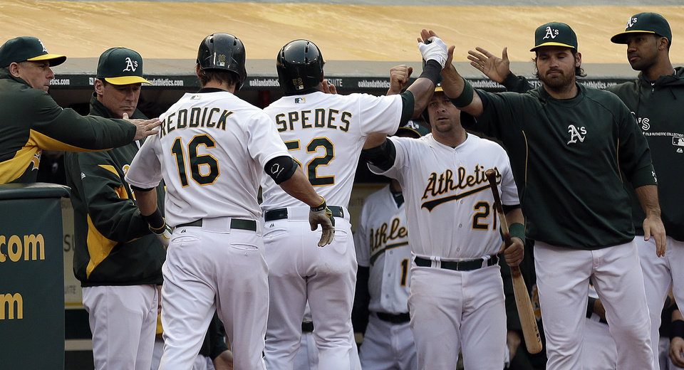 Photo - Oakland Athletics' Yoenis Cespedes (52) is congratulated after scoring against the Toronto Blue Jays in the first inning of a baseball game Monday, July 29, 2013, in Oakland, Calif. Cespedes scored on a sacrifice fly by Josh Reddick (16). (AP Photo/Ben Margot)