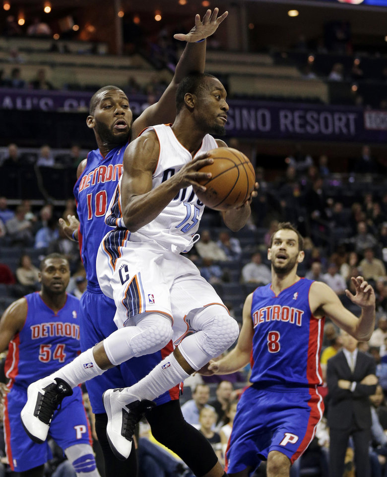 Charlotte Bobcats' Kemba Walker (15) looks to pass as Detroit Pistons' Greg Monroe (10) and Jose Calderon (8) defend during the first half of an NBA basketball game in Charlotte, N.C., Wednesday, Feb. 20, 2013. (AP Photo/Chuck Burton)