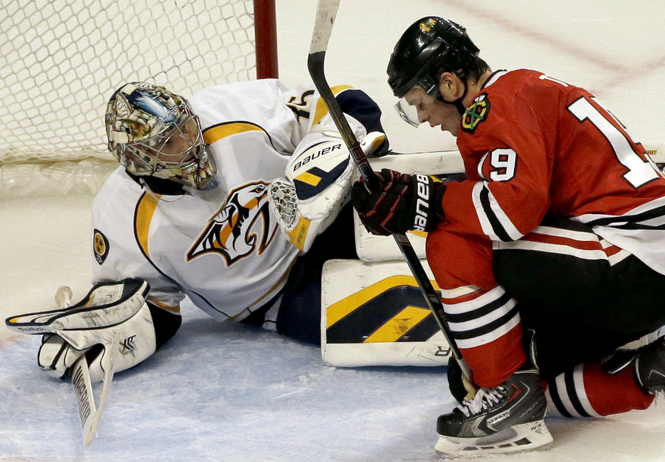 Photo - Chicago Blackhawks' Jonathan Toews (19), right, reacts after missing a shot as Nashville Predators goalie Pekka Rinne (35) looks on during the third period of an NHL hockey game in Chicago, Friday, March 14, 2014. The Predators won 3-2. (AP Photo/Nam Y. Huh)