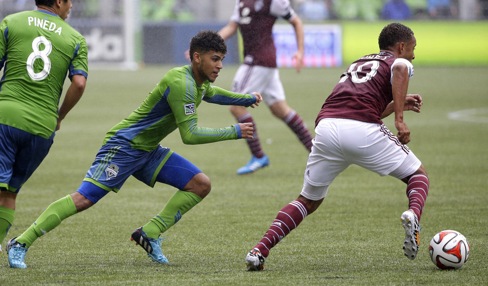Photo - Seattle Sounders' DeAndre Yedlin, second from left, pursues Colorado Rapids' Gabriel Torres, right, in the second half of an MLS soccer match, Saturday, Aug. 30, 2014, in Seattle. The Sounders defeated the Rapids 1-0. (AP Photo/Ted S. Warren)