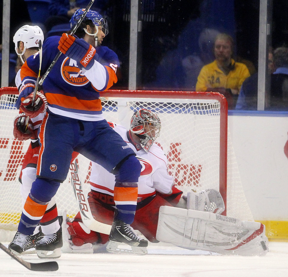 Photo - Carolina Hurricanes goalie Cam Ward (30) makes a save on a shot by New York Islanders left wing Matt Moulson (26) during the first period of an NHL hockey game at the Nassau Coliseum in Uniondale, N.Y., Monday, Feb.11, 2013. (AP Photo/Paul J. Bereswill)