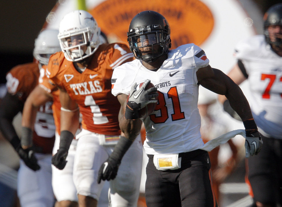Photo - Oklahoma State's Jeremy Smith (31) runs upfield as Texas' Mike Davis (1) chases him during second half of a college football game between the Oklahoma State University Cowboys (OSU) and the University of Texas Longhorns (UT) at Darrell K Royal-Texas Memorial Stadium in Austin, Texas, Saturday, Oct. 15, 2011. Photo by Sarah Phipps, The Oklahoman