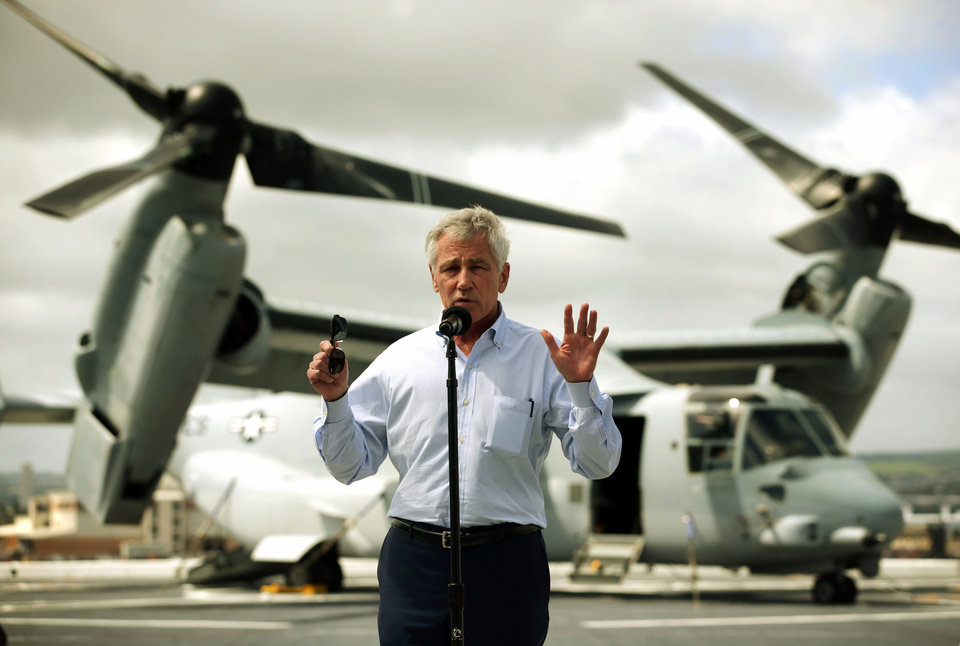 Photo - U.S. Secretary of Defense Chuck Hagel speaks about the shooting at Fort Hood during a news conference on the flight deck of the USS Anchorage (LPD-23), an amphibious transport dock ship, after a tour with his counterparts from Southeast Asia April 2, 2014 at Joint Base Pearl Harbor-Hickam in Honolulu, Hawaii. Secretary Hagel is in Hawaii to host a meeting of defense ministers from the Association of Southeast Asian Nations (ASEAN). A MV-22 Osprey tiltrotor V/STOL aircraft is in the background, (AP Photo/Alex Wong, Pool)