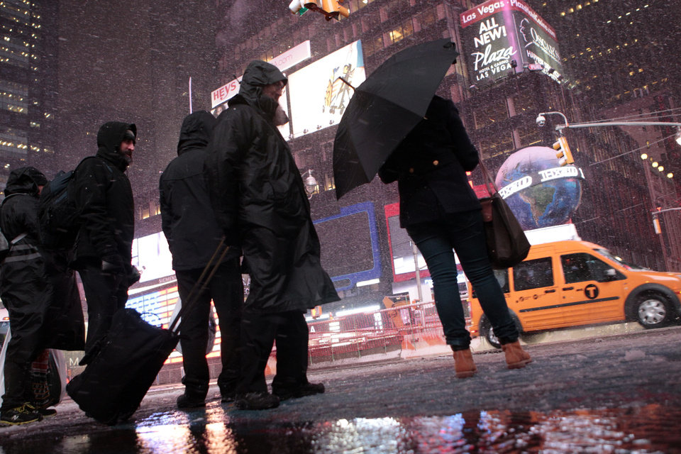 Photo -   Pedestrians walk through Times Square as it snows Wednesday, Nov. 7, 2012, in New York. Coastal residents of New York and New Jersey faced new warnings to evacuate their homes and airlines canceled hundreds of flights as a new storm arrived Wednesday, only a week after Superstorm Sandy left dozens dead and millions without power. (AP Photo/Frank Franklin II)