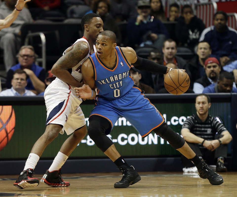 Photo - Oklahoma City Thunder point guard Russell Westbrook (0) works against Atlanta Hawks point guard Jeff Teague in the first half of an NBA basketball game Tuesday, Dec. 10, 2013, in Atlanta. (AP Photo/John Bazemore)